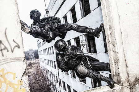 Spec ops police officers SWAT during rope exercises with weapons Imagens