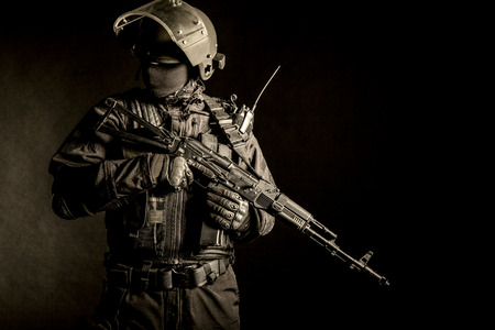 Russian special forces operator in black uniform and bulletproof helmet Stok Fotoğraf