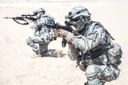 assault forces: United States paratroopers airborne infantrymen in action in the desert Stock Photo
