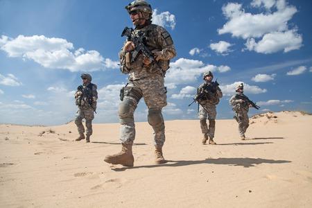 acion: Estados Unidos paracaidistas de infantería en el aire en la acción en el desierto Foto de archivo