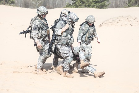 military special forces: United States paratroopers airborne infantrymen in the desert rescuing their brother