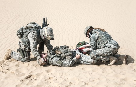 United States paratroopers airborne infantrymen in the desert rescuing their brother