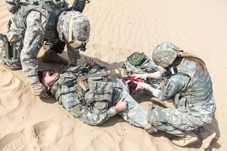 military forces: United States paratroopers airborne infantrymen in the desert rescuing their brother