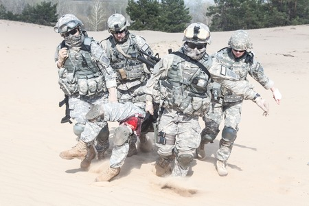 recon: United States paratroopers airborne infantrymen in the desert rescuing their brother