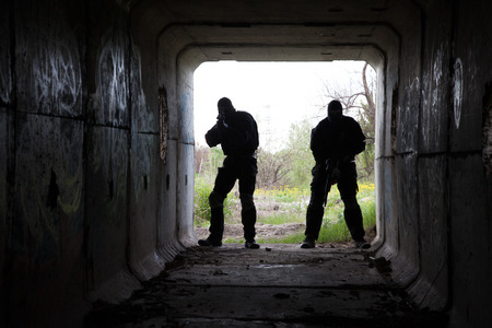 weapon: Silhouette of special forces operators with weapons in the tunnel