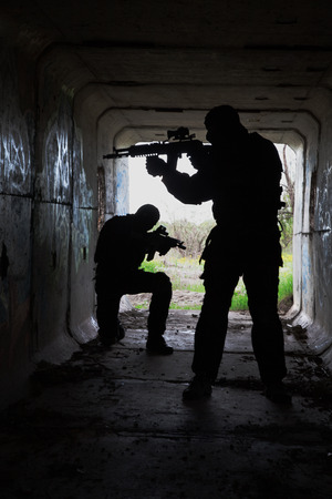 assault forces: Silhouette of special forces operators with weapons in the tunnel