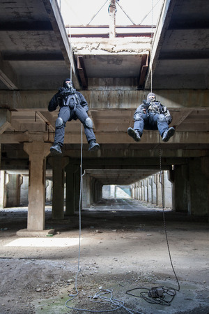 assault: Special forces operators during assault rappeling with weapons Stock Photo