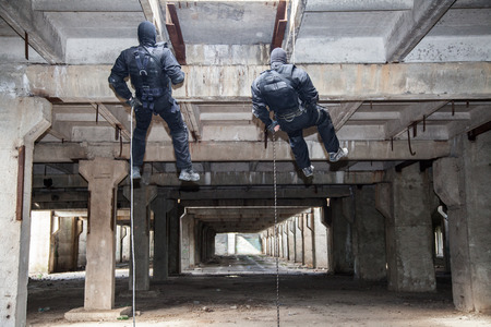 rappeling: Special forces operators during assault rappeling with weapons Stock Photo