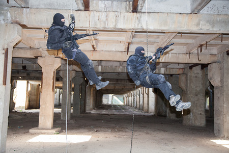 police unit: Special forces operators during assault rappeling with weapons Stock Photo