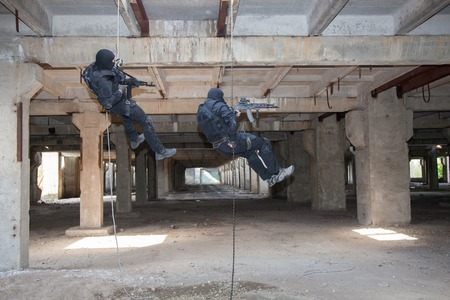 weapon: Special forces operators during assault rappeling with weapons Stock Photo