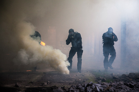 Special forces operator in black uniform in the smoke