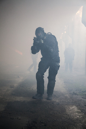 police unit: Special forces operator in black uniform in the smoke