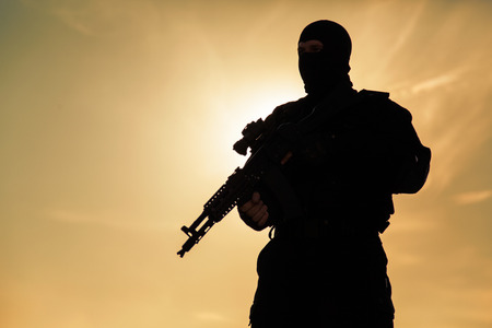 special operations: Silhouette of special forces operators with weapons Stock Photo