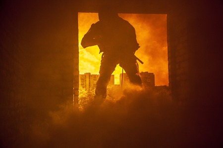 swat teams: Assault team member comes through the window on fire Stock Photo
