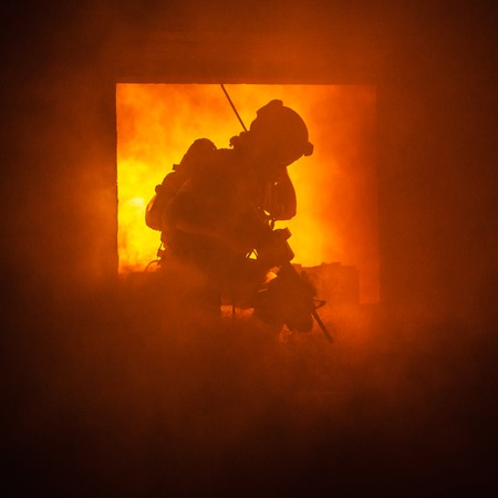 rappelling: Assault team member comes through the window on fire Stock Photo