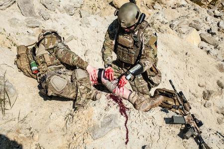 soldado: Ejército de Estados Unidos médico guardabosques tratamiento de las heridas de su compañero herido en armas en las montañas