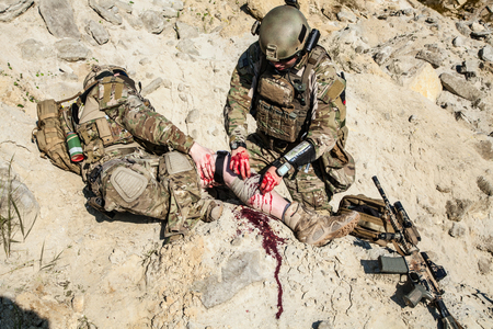 United States Army ranger medic treating the wounds of his injured fellow in arms in the mountains