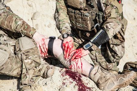 wojenne: Armia Stanów Zjednoczonych ranger medyk leczenia rany jego rannych kolegów z bronią w ręku w górach