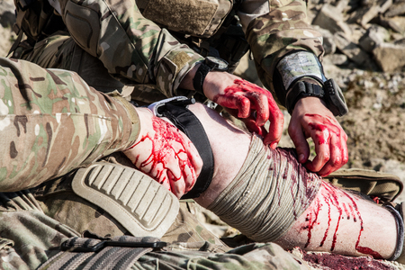 medics: United States Army ranger medic treating the wounds of his injured fellow in arms in the mountains
