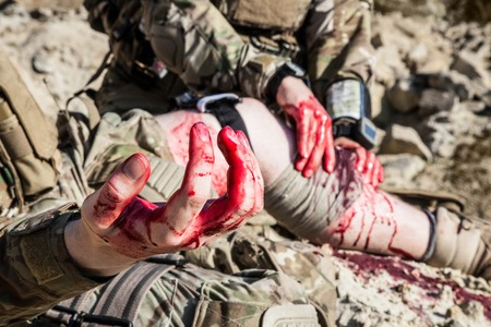 United States Army Ranger Sanitäter behandeln die Wunden der seinen verletzten Kollegen in den Armen in den Bergen Standard-Bild - 46210446