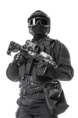 Spec ops police officer SWAT in black uniform and face mask studio shot