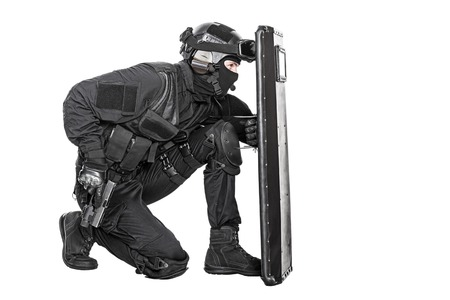 Spec ops police officer SWAT with ballistic shield studio shot