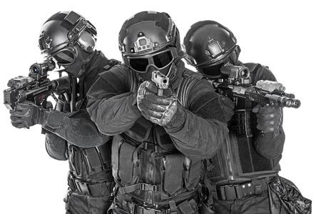 Spec ops police officers SWAT in black uniform and face mask studio shot Foto de archivo