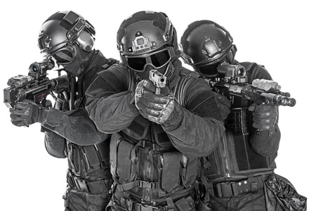 Spec ops police officers SWAT in black uniform and face mask studio shot Banco de Imagens