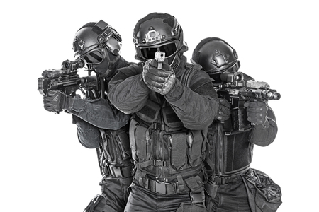Spec ops police officers SWAT in black uniform and face mask studio shot Foto de archivo