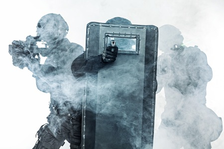 Police officers SWAT with ballistic shield in the smoke studio shot