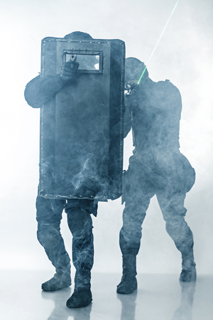 anti nato: Police officers SWAT with ballistic shield in the smoke studio shot