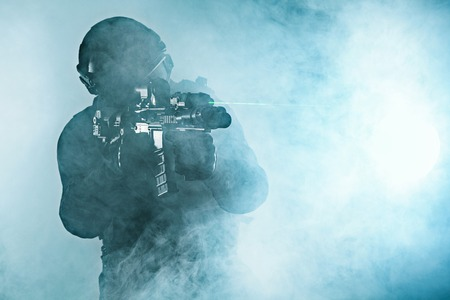 military special forces: Police officer SWAT in black uniform in the smoke studio shot Stock Photo