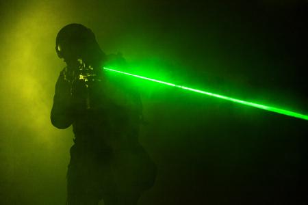 Politieman SWAT in zwart uniform in de rook met laser bezienswaardigheden Stockfoto