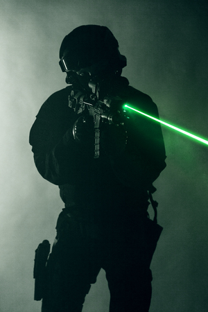 swat: Police officer SWAT in black uniform in the smoke with laser sights Stock Photo