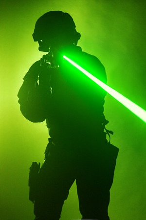 Police officer SWAT in black uniform in the smoke with laser sights Stock Photo