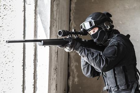 Spec ops politieman SWAT in zwart uniform en masker in actie