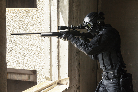 anti nato: Spec ops police officer SWAT in black uniform and face mask in action