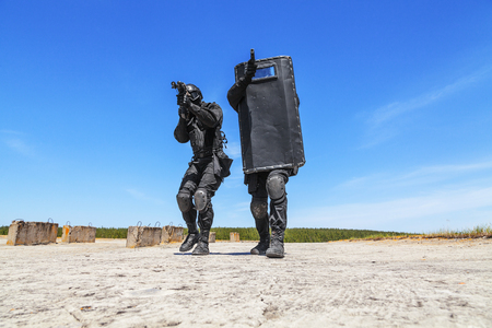 Spec ops police officers SWAT with ballistic shield in action