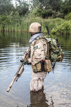navy seal: Member of Navy SEAL Team crossing the river with weapons