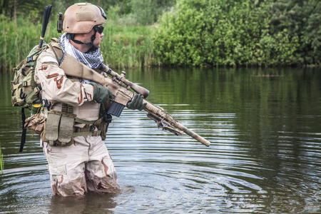 weapon: Member of Navy SEAL Team crossing the river with weapons