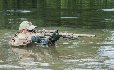 recon: Member of Navy SEAL Team crossing the river with weapons