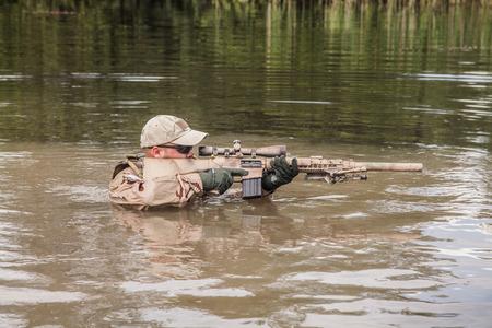 武器で川を渡る海軍シール チームのメンバー
