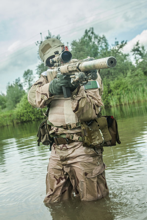 marksman: Member of Navy SEAL Team crossing the river with weapons