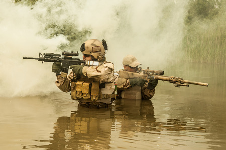 Navy SEALs crossing the river with weapons