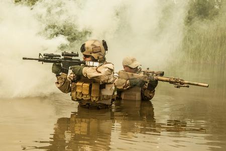 Navy SEALs oversteken van de rivier met wapens