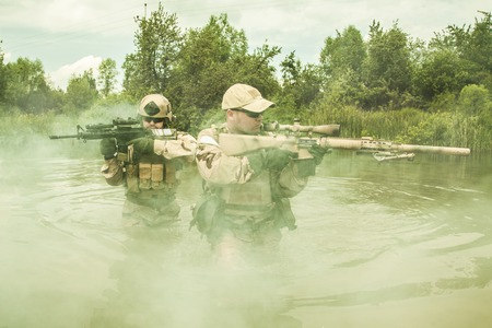 recon: Navy SEALs crossing the river with weapons