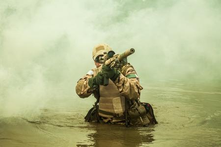 sellos: Miembro de la Marina SEAL Team cruzando el río con armas Foto de archivo