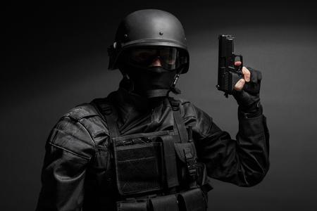 Spec ops police officer SWAT in black uniform with pistol studio Stockfoto