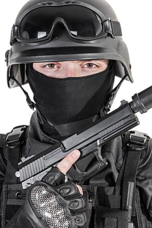 swat: Spec ops police officer SWAT in black uniform with pistol studio Stock Photo