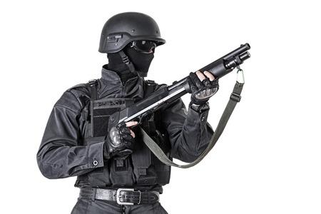 Spec ops police officer SWAT in black uniform with shotgun studio shot